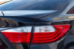 特写镜头身体和一辆黑汽车的红白的车灯的设计的后面在洗涤以后是干净和发光的 库存照片