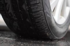 特写镜头车胎坐湿沥青 免版税库存图片