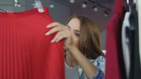 特写镜头选择在精品店的射击了可爱的女孩衣裳 她审阅时兴的上面、套头衫和裙子 影视素材
