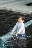 特写镜头逗人喜爱的亚洲孩子在游泳池被构造的背景中享用在泰国的夏天 库存图片