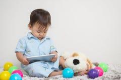 特写镜头逗人喜爱的亚洲孩子看看片剂在家在有玩偶和五颜六色的球和水泥墙壁的灰色地毯构造了背景w 免版税库存图片