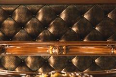 特写镜头金织品布置了床头板有按钮纺织品背景,减速火箭的时髦的卧室家具与 免版税库存图片