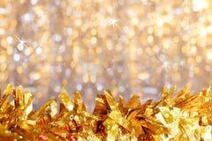 特写镜头金黄发光的闪亮金属片下来在金黄bokeh背景的前景与星号和拷贝空间的 免版税图库摄影