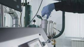 特写镜头雇员倾吐液体样品入在液体分析仪的容器 股票录像