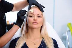 特写镜头面孔,得到在秀丽诊所的女性客户水合的做法 有化妆刷子的Hands医生 免版税库存照片