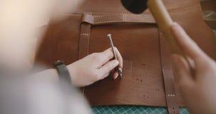 特写镜头顶视图做在手工制造大皮包的被射击专业女性手孔与锤子和手动打孔机 股票录像