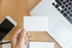 特写镜头顶视图显示空白的白色名片和使用现代膝上型计算机和手机在木桌上的照片妇女 图库摄影
