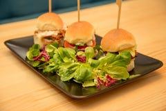 特写镜头鲜美微型汉堡用在小餐馆桌上的沙拉 库存图片