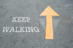 特写镜头黄色绘了在水泥街道地板上的箭头标志与白色保留走的词被构造的背景 免版税图库摄影