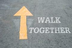特写镜头黄色绘了在水泥街道地板上的箭头标志与白色步行一起措辞织地不很细背景 免版税库存图片