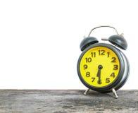 特写镜头黑和黄色闹钟为装饰展示一半通过六或6:30 a M 在白色backgro隔绝的老棕色木书桌上 免版税库存照片