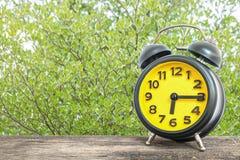 特写镜头黑和黄色闹钟为装饰展示每处所通过六或6:15 a M 在绿色叶子的老棕色木书桌上在t 库存图片