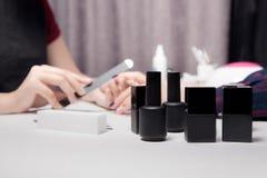 特写镜头黑色瓶子,瓶,容器指甲油 处理创造修指甲美好的女性手 免版税库存照片