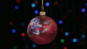 特写镜头,一个红色圣诞节球的自转在一条金黄绳索垂悬了 圣诞节装饰新年度 影视素材