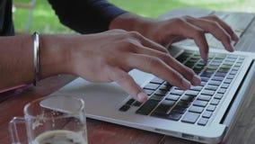 特写镜头,印度人的手在夏天公园键入在膝上型计算机键盘的文本,坐在表上 股票视频