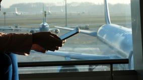 特写镜头,在机场,在候诊室,以俯视飞机的窗口为背景和 股票视频