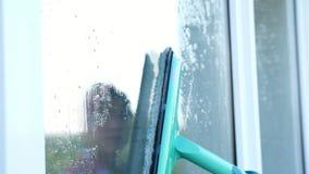 特写镜头,在玻璃窗是被反射的微笑的白种人美丽的妇女,手套的,清洁,洗涤物窗口  股票录像