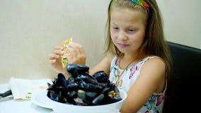 特写镜头,在餐馆,孩子女孩在桌上服务了一个大碗,煮熟的开放蓝色贻贝板材  孩子 影视素材