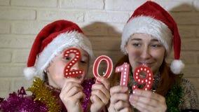 特写镜头,孩子,举行2019个数字和使用与他们的两女孩 他们在红色圣诞老人帽子坐长沙发 影视素材
