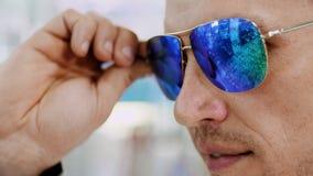 特写镜头,尝试在蓝色太阳镜的英俊的年轻人画象在光学商店,眼镜师零售店 在玻璃 影视素材