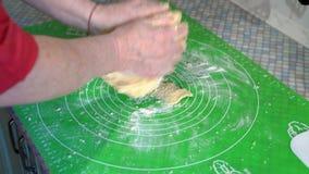 特写镜头,年长仔细妇女混合烘烤面团的手在厨房用桌上的 股票视频