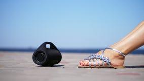 特写镜头,微型音乐bluetooth便携式的黑圆筒无线扩音器 在银色凉鞋的女性腿,与明亮 股票视频