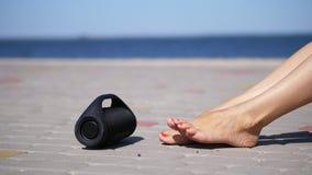 特写镜头,微型音乐bluetooth便携式的黑圆筒无线扩音器 在银色凉鞋的女性腿,与明亮 影视素材