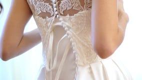 特写镜头,新娘费 新娘为婚礼打扮 女傧相系带有丝带的白色鞋带礼服 婚姻 股票录像