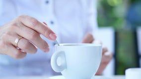 特写镜头,有热奶咖啡的白色杯子,与浓乳脂状的泡沫和蛋白软糖 妇女` s手慢慢地引起饮料与 股票视频