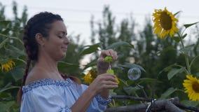 特写镜头,有辫子的美丽的村庄妇女在庭院里让肥皂泡 股票录像