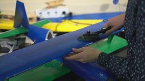 特写镜头,男小学生使在刻痕航空器模型铺平的铁光滑 股票视频