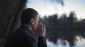 特写镜头,男性喝热的茶和沉思地神色在坐在湖附近的太阳的日落在森林里 股票视频