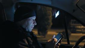 特写镜头,看在智能手机的大人联络在晚上在坐在汽车的轮子的停放的公园 股票录像