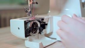 特写镜头,裁缝手去掉有螺纹的一个片盘从一台缝纫机 慢的行动 股票视频