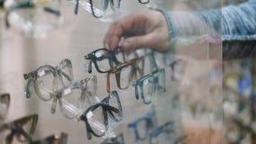 特写镜头,陈列室在光学商店,光学,眼镜师零售店,镜片购物,很多玻璃,框架,人` s 股票视频