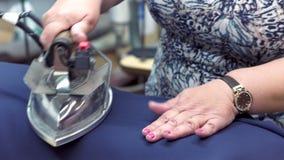 特写镜头:使用古板的铁,裁缝妇女蒸夹克 妇女的手拿着铁并且使光滑 股票录像