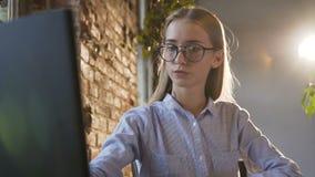 特写镜头 使用现代计算机,美丽的年轻女商人佩带的玻璃运作 确信的女性雇员 股票录像