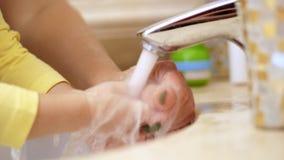 特写镜头 儿童现有量s 孩子洗她的手在轻拍下 妈妈帮助 在卫生间里 股票视频