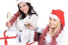 特写镜头 圣诞老人帽子的三个少妇戴圣诞节香槟礼物和眼镜的  免版税库存照片