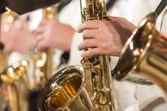特写镜头 在一套白色衣服的一只人` s手在爵士乐队的一支金萨克斯管 浅深度的域 库存图片