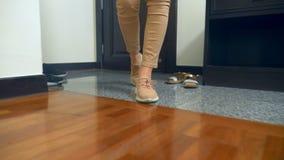 特写镜头 在运动鞋的女性腿 妇女走入房子并且走通过孩子和她的丈夫驱散的鞋子 股票视频