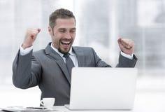 特写镜头 坐在一台开放膝上型计算机前面的愉快的商人 库存图片