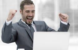 特写镜头 坐在一台开放膝上型计算机前面的愉快的商人 免版税库存照片