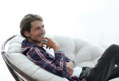 特写镜头 微笑的人在一把大舒适的椅子休息 库存图片