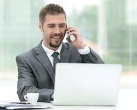 特写镜头 成功的商人研究膝上型计算机和谈话在电话 免版税库存图片