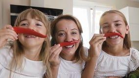特写镜头 有她的两个女儿的可爱的母亲由红辣椒辣椒做一根髭并且有乐趣微笑的摆在  影视素材