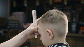 特写镜头 有逗人喜爱的客户孩子的美发师在理发店 使用整理者和梳子的理发师在理发店 美丽 影视素材