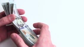特写镜头 男性手培养和整洁地堆积堆美元 一在白色背景的一千美元 财富和 股票录像