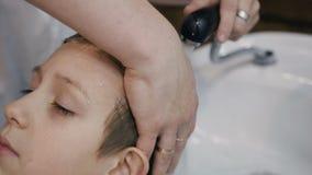 特写镜头 美发师在美容院或理发店洗年轻人的头发 美发师人洗涤的头发  股票视频