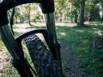 特写镜头 自行车的轮子和阴影在森林里 免版税库存图片